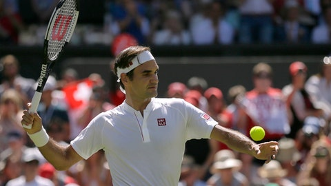 Roger Federer of Switzerland sends a ball into the tribunes after defeating Serbia's Dusan Lajovic, in their Men's Singles first round match at the Wimbledon Tennis Championships in London, Monday July 2, 2018. (AP Photo/Tim Ireland)