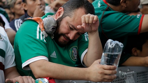 A Mexico soccer fans reacts to Brazil's goal during a live broadcast of the Russia World Cup game in Mexico City's Zocalo plaza, Monday, July 2, 2018. (AP Photo/Anthony Vazquez)