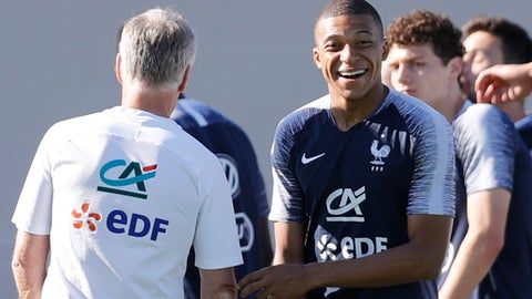 France's Kylian Mbappe smiles as he jokes with his headcoach Didier Deschamps, back, during a training session at the 2018 soccer World Cup in Glebovets, Russia, Monday, July 2, 2018. (AP Photo/David Vincent)