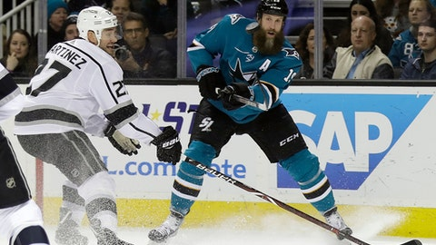 FILE - In this Dec. 23, 2017, file photo, San Jose Sharks center Joe Thornton, right, passes as Los Angeles Kings defenseman Alec Martinez (27) closes in during the first period of an NHL hockey game in San Jose, Calif. The Sharks have re-signed Thornton to a one-year contract. The team announced the deal on Thornton's 39th birthday Monday, July 2, 2018. (AP Photo/Marcio Jose Sanchez, File)