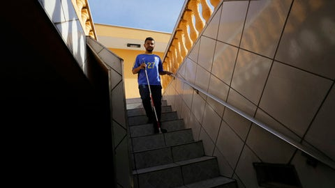 Brazil soccer fan Carlos Junior, who is both deaf and blind, leaves his home to watch a live broadcast of the match between Brazil and Mexico during the 2018 soccer World Cup, in Sao Paulo, Brazil, Monday, July 2, 2018. The 31-year-old who is deaf and blind experienced the game with the help of interpreters using touch communication and a model soccer field to recount the passes, goals and fouls of the national team.  (AP Photo/Nelson Antoine)