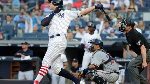 New York Yankees' Aaron Judge follows through on a home run during the first inning of a baseball game as Atlanta Braves catcher Kurt Suzuki, center, and home plate umpire Mike Estabrook watch Monday, July 2, 2018, in New York. (AP Photo/Frank Franklin II)