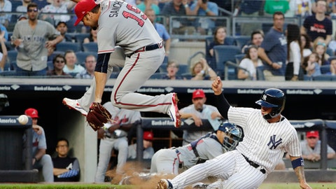 New York Yankees' Gleyber Torres (25) slides past Atlanta Braves starting pitcher Anibal Sanchez (19) to score on a wild pitch during the third inning of a baseball game Monday, July 2, 2018, in New York. (AP Photo/Frank Franklin II)