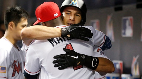 Miami Marlins' J.T. Realmuto gets a hug from Cameron Maybin (1) after Realmuto hit a home run during the fifth inning of a baseball game against the Tampa Bay Rays, Monday, July 2, 2018, in Miami. (AP Photo/Wilfredo Lee)