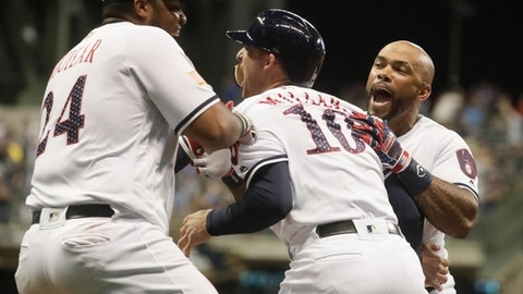 Milwaukee Brewers' Brad Miller is congratulated by teammates Jesus Aguilar (24) and Eric Thames after his walk off walk during the 10th inning of a baseball game against the Minnesota Twins Monday, July 2, 2018, in Milwaukee. The Brewers won 6-5. (AP Photo/Morry Gash)