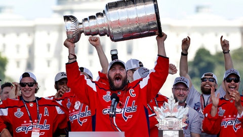 "FILE - In this Tuesday, June 12, 2018 file photo Washington Capitals Alex Ovechkin, from Russia, holds up the Stanley Cup trophy during the NHL hockey team's Stanley Cup victory celebration, at the National Mall in Washington. Alex Ovechkin is bringing the Stanley Cup to the World Cup. Fresh off winning the NHL title, the Washington Capitals forward is taking the trophy to Moscow on Saturday, where it will be exhibited at a ""fan fest"" public viewing site ahead of Russia's quarterfinal game against Croatia. (AP Photo/Jacquelyn Martin)"
