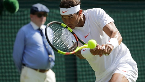 Rafael Nadal, of Spain, returns the ball to Dudi Sela, of Israel, during their men's singles match, on the second day of the Wimbledon Tennis Championships in London, Tuesday July 3, 2018. (AP Photo/Ben Curtis)