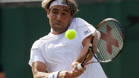 Marcos Baghdatis of Cyprus plays a return shot to Dominic Thiem of Austria during their men's singles match on the second day at the Wimbledon Tennis Championships in London, Tuesday July 3, 2018. (AP Photo/Kirsty Wigglesworth)