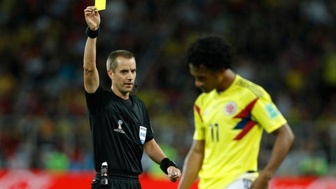 Referee Mark Geiger from the US shows a yellow card to Colombia's Juan Cuadrado during the round of 16 match between Colombia and England at the 2018 soccer World Cup in the Spartak Stadium, in Moscow, Russia, Tuesday, July 3, 2018. (AP Photo/Victor R. Caivano)
