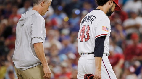 Texas Rangers trainer Kevin Harmon, left, escorts relief pitcher Tony Barnette (43) as he leaves after suffering an injury during the eighth inning of the team's baseball game against the Houston Astros, Tuesday, July 3, 2018, in Arlington, Texas. Houston won 5-3. (AP Photo/Brandon Wade)