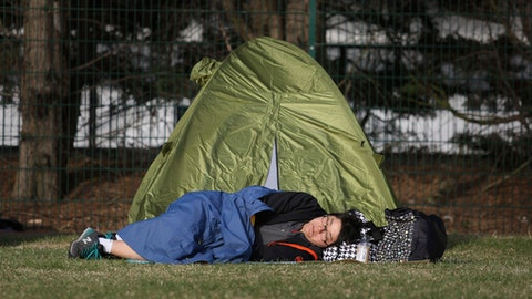A person sleeps by their tent before joining the entrance queue in Wimbledon Park on day three at the Wimbledon Tennis Championships in London, Wednesday July 4, 2018. (Philip Toscano/PA via AP)