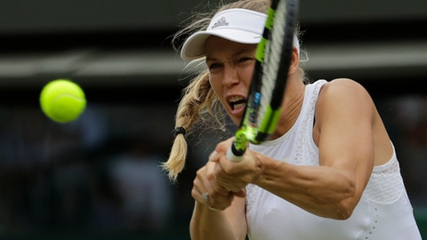 Caroline Wozniacki of Denmark plays a return to Ekaterina Makarova of Russia during their women's singles match on the third day at the Wimbledon Tennis Championships in London, Wednesday July 4, 2018. (AP Photo/Ben Curtis)