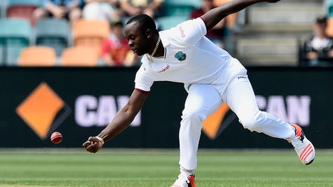 FILE - In this Thursday, Dec. 10, 2015 file photo, West Indies' bowler Kemar Roach fields off his own bowling against Australia during their cricket test match in Hobart, Australia. Bangladesh was all out for only 43 before lunch on the opening day as West Indies right-arm quick Kemar Roach destroyed the tourists with figures of 5-8 in the first test on Wednesday, July 4, 2018.(AP Photo/Andy Brownbill, file)