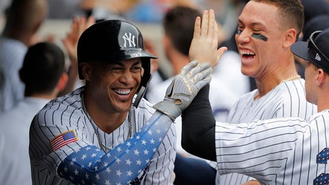 New York Yankees' Giancarlo Stanton, left, celebrates with teammates, including Aaron Judge, rear right, after hitting a three-run home run against the Atlanta Braves during the third inning of a baseball game, Wednesday, July 4, 2018, in New York. (AP Photo/Julie Jacobson)
