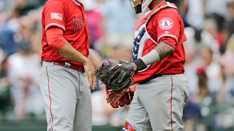 Los Angeles Angels closing pitcher Blake Parker and catcher Martin Maldonado greet one another after the team's 7-4 win over the Seattle Mariners in a baseball game Wednesday, July 4, 2018, in Seattle. (AP Photo/John Froschauer)