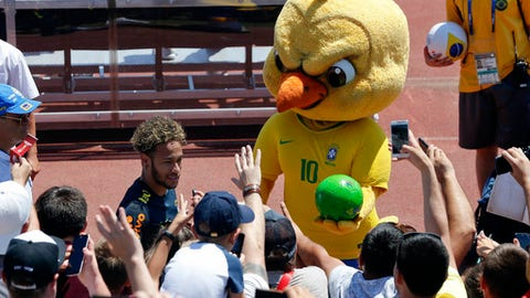 """FILE - In this Tuesday, June 12, 2018 file photo Brazil's mascot holds a soccer ball as fans cheer Brazil's Neymar as he leaves a training session in Sochi, Russia. It took an angry-looking bird to get Brazilians hooked on their World Cup mascot. Brazil historically never fully embraced the tradition of mascots in sports, but things changed when the soccer federation _ inspired in part by Chicago Bull's """"Benny the Bull"""" _ turned its cute-looking """"Canary"""" into a mean figure that represents the fans' anger following the humiliating home loss at the World Cup four years ago.(AP Photo/Andre Penner, File)"""