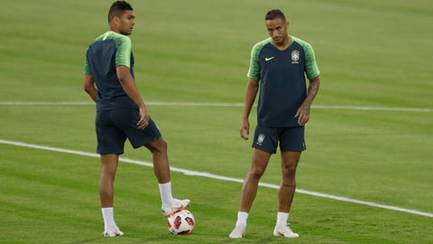 Brazil's Danilo, right, and Casemiro wait for the start of the official training session of the Brazil team prior to the quarter final match between Brazil and Belgium at the 2018 soccer World Cup at the Tsentralny stadium in Kazan, Russia, Thursday, July 5, 2018. (AP Photo/Matthias Schrader)