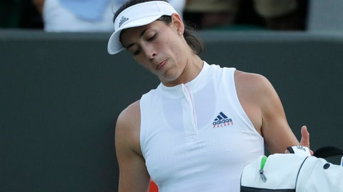 Spain's Garbine Muguruza leaves the court after losing her women's singles match against Alison Van Uytvanck of Belgium, on the fourth day at the Wimbledon Tennis Championships in London, Thursday July 5, 2018. (AP Photo/Ben Curtis)