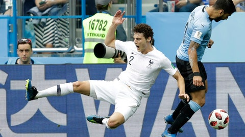 France's Benjamin Pavard, left, takes a tumble as he competes for the ball with Uruguay's Luis Suarez during the quarterfinal match between Uruguay and France at the 2018 soccer World Cup in the Nizhny Novgorod Stadium, in Nizhny Novgorod, Russia, Friday, July 6, 2018. (AP Photo/Natacha Pisarenko)