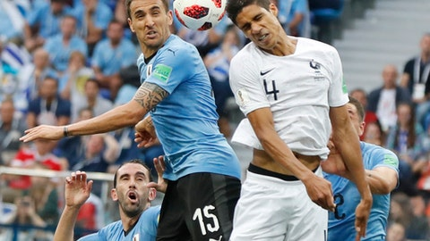 France's Raphael Varane, center right, and Uruguay's Matias Vecino, center left, challenge for the ball during the quarterfinal match between Uruguay and France at the 2018 soccer World Cup in the Nizhny Novgorod Stadium, in Nizhny Novgorod, Russia, Friday, July 6, 2018. (AP Photo/Petr David Josek)