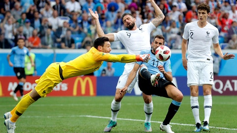 France goalkeeper Hugo Lloris, front left, and Uruguay's Cristhian Stuani, front right, challenge for the ball during the quarterfinal match between Uruguay and France at the 2018 soccer World Cup in the Nizhny Novgorod Stadium, in Nizhny Novgorod, Russia, Friday, July 6, 2018. (AP Photo/David Vincent)