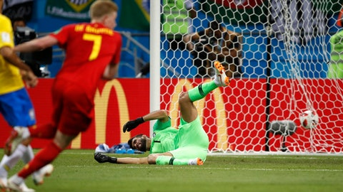 Brazil goalkeeper Alisson sits on the pitch after Belgium's Kevin De Bruyne, left, scored his side's second goal during the quarterfinal match between Brazil and Belgium at the 2018 soccer World Cup in the Kazan Arena, in Kazan, Russia, Friday, July 6, 2018. (AP Photo/Francisco Seco)