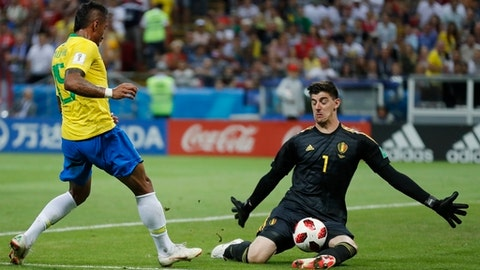 Belgium goalkeeper Thibaut Courtois, right, makes a save as Brazil's Paulinho tries to score during the quarterfinal match between Brazil and Belgium at the 2018 soccer World Cup in the Kazan Arena, in Kazan, Russia, Friday, July 6, 2018. (AP Photo/Frank Augstein)
