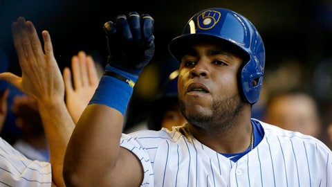 Milwaukee Brewers' Jesus Aguilar is congratulated in the dugout after hitting a three-run home run during the third inning of the team's baseball game against the Atlanta Braves on Friday, July 6, 2018, in Milwaukee. (AP Photo/Aaron Gash)