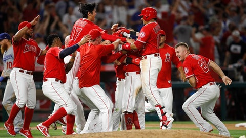 Los Angeles Angels celebrate a walk-off single by Ian Kinsler during a baseball game against the Los Angeles Dodgers, Friday, July 6, 2018, in Anaheim, Calif. The Angels won 3-2. (AP Photo/Jae C. Hong)