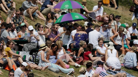 Spectators sit on Murray Mound on the sixth day at the Wimbledon Tennis Championships in London, Saturday July 7, 2018. (AP Photo/Ben Curtis)