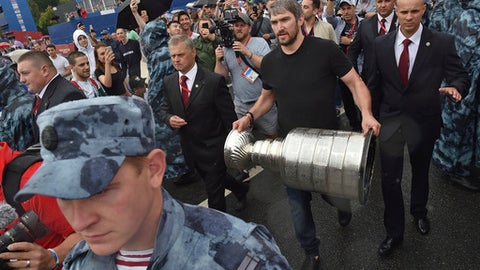 "Washington Capitals Alex Ovechkin, from Russia, holds the Stanley Cup trophy at the fan zone in Moscow ahead of the the quarterfinal match between Russia and Croatia at the 2018 soccer World Cup that is being played in the Fisht Stadium, in Sochi, Russia, Saturday, July 7, 2018. Ovechkin is bringing the Stanley Cup to the World Cup. Fresh off winning the NHL title, the Washington Capitals forward is taking the trophy to Moscow on Saturday, where it will be exhibited at a ""fan fest"" public viewing site ahead of Russia's quarterfinal game against Croatia. (AP Photo/Dmitry Serebryakov)"
