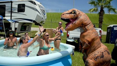Joseph Gullett, right, dressed in a dinosaur suit jokes with fans relaxing in a pool cooling off in a camping area before a NASCAR cup series auto race at Daytona International Speedway, Saturday, July 7, 2018, in Daytona Beach, Fla. (AP Photo/Phelan M. Ebenhack)