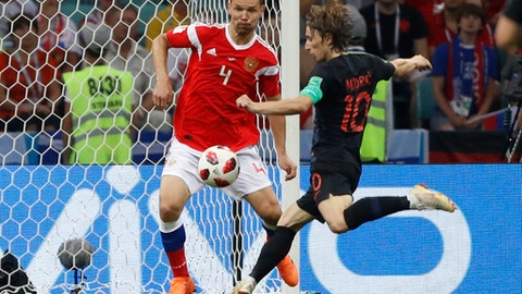 Croatia's Luka Modric, right, vies for the ball with Russia's Sergei Ignashevich during the quarterfinal match between Russia and Croatia at the 2018 soccer World Cup in the Fisht Stadium, in Sochi, Russia, Saturday, July 7, 2018. (AP Photo/Darko Bandic)
