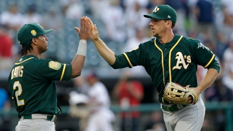Oakland Athletics' Stephen Piscotty, right, is congratulated by Khris Davis after the Athletics defeated the Cleveland Indians 6-3 in 11 innings of a baseball game, Saturday, July 7, 2018, in Cleveland. (AP Photo/Tony Dejak)