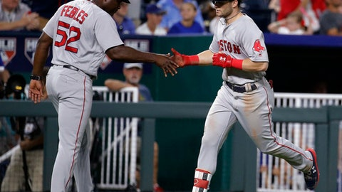 Boston Red Sox's Andrew Benintendi celebrates with third base coach Carlos Febles (52) after hitting a solo home run during the eighth inning of a baseball game against the Kansas City Royals on Saturday, July 7, 2018, in Kansas City, Mo. (AP Photo/Charlie Riedel)
