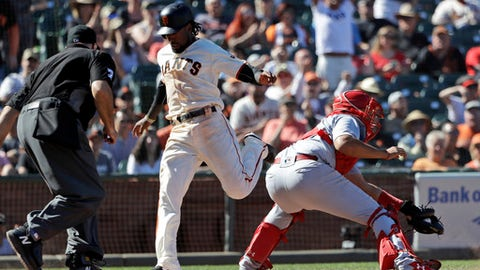 San Francisco Giants' Alen Hanson, center, scores past St. Louis Cardinals catcher Francisco Pena, right, after a ground ball by Hunter Pence and a fielding error by the Cardinals during the eighth inning of a baseball game Sunday, July 8, 2018, in San Francisco. (AP Photo/Marcio Jose Sanchez)