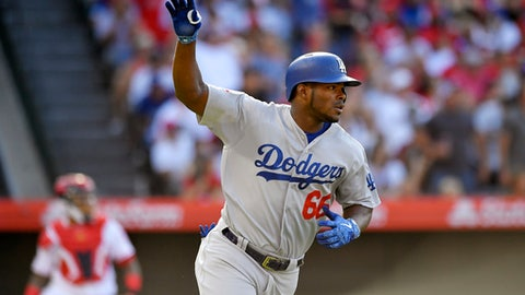 Los Angeles Dodgers' Yasiel Puig, right, celebrates as he hits a three-run home run while Los Angeles Angels catcher Martin Maldonado watches during the second inning of a baseball game Sunday, July 8, 2018, in Anaheim, Calif. (AP Photo/Mark J. Terrill)