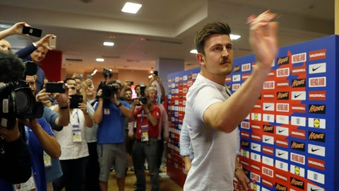 England's Harry Maguire plays a game of darts as the media looks on before a press conference for the England team at the 2018 soccer World Cup, in Repino near St. Petersburg, Russia, Monday, July 9, 2018. (AP Photo/Alastair Grant)