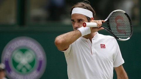 Roger Federer of Switzerland wipes his face during his men's singles match against France's Adrian Mannarino, on day seven of the Wimbledon Tennis Championships, in London, Monday July 9, 2018. (AP Photo/Tim Ireland)