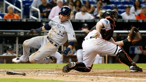 Milwaukee Brewers' Christian Yelich (22) slides into home to score on a single by Travis Shaw, as Miami Marlins catcher Bryan Holaday waits for the throw during the eighth inning of a baseball game, Monday, July 9, 2018, in Miami. The Marlins defeated the Brewers 4-3 in 10 innings. (AP Photo/Wilfredo Lee)