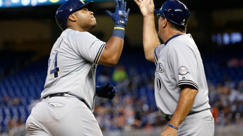 Milwaukee Brewers' Jesus Aguilar (24) celebrates with third base coach Ed Sedar after hitting a home run during the eighth inning of a baseball game against the Miami Marlins, Monday, July 9, 2018, in Miami. The Marlins defeated the Brewers 4-3 in 10 innings. (AP Photo/Wilfredo Lee)