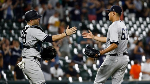 New York Yankees catcher Austin Romine, left, and relief pitcher Giovanny Gallegos high-five after closing out the second baseball game of a doubleheader against the Baltimore Orioles, Monday, July 9, 2018, in Baltimore. New York won 10-2. (AP Photo/Patrick Semansky)