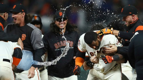 San Francisco Giants' Pablo Sandoval, center, celebrates after making the game-winning hit in the 11th inning of a baseball game against the Chicago Cubs, Monday, July 9, 2018, in San Francisco. The Giants won 2-1. (AP Photo/Ben Margot)