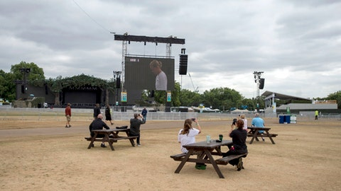 People sit watching wimbledon on the big screen as final preparations are made at British Summer Time (BST) event in Hyde Park, London, where 30,000 football fans are expected to watch England's World Cup semi-final against Croatia, Tuesday July 10, 2018.  England will play Croatia in the World Cup soccer semi-final on Wednesday. (David Mirzoeff/PA via AP)