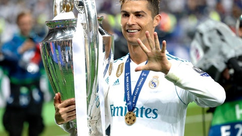 FILE - In this Saturday, May 26, 2018 file photo Real Madrid's Cristiano Ronaldo celebrates with the trophy after winning the Champions League Final soccer match between Real Madrid and Liverpool at the Olimpiyskiy Stadium in Kiev, Ukraine. (AP Photo/Pavel Golovkin)