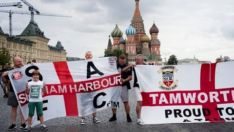 England soccer fans pose for a photo with their club banners in Red Square during the 2018 soccer World Cup in Moscow, Russia, Tuesday, July 10, 2018. (AP Photo/Alexander Zemlianichenko)