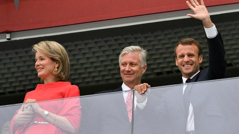 French President Emmanuel Macron, right, waves as he stands beside King Philippe of Belgium and Queen Mathilde, left, prior to the semifinal match between France and Belgium at the 2018 soccer World Cup in the St. Petersburg Stadium in St. Petersburg, Russia, Tuesday, July 10, 2018. (AP Photo/Martin Meissner)