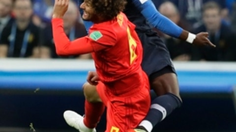 Belgium's Marouane Fellaini and France's Samuel Umtiti, top, vie for the ball during the semifinal match between France and Belgium at the 2018 soccer World Cup in the St. Petersburg Stadium, in St. Petersburg, Russia, Tuesday, July 10, 2018. (AP Photo/Petr David Josek)
