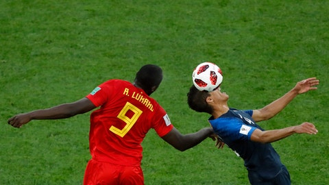Belgium's Romelu Lukaku, left, jumps for the ball with France's Raphael Varane during the semifinal match between France and Belgium at the 2018 soccer World Cup in the St. Petersburg Stadium in St. Petersburg, Russia, Tuesday, July 10, 2018. (AP Photo/Pavel Golovkin)