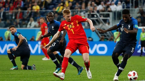 Belgium's Kevin De Bruyne, center, and France's Samuel Umtiti challenge for the ball during the semifinal match between France and Belgium at the 2018 soccer World Cup in the St. Petersburg Stadium in, St. Petersburg, Russia, Tuesday, July 10, 2018. (AP Photo/Frank Augstein)